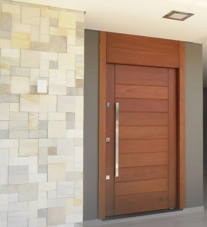 Fachada da casa com porta pivotante de madeira