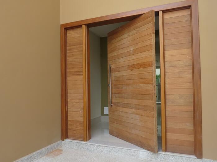 Porta de madeira com duas partes fixas laterais complementando o vão