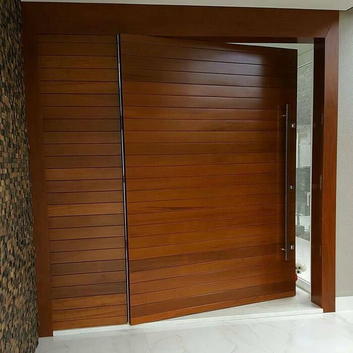 Porta de madeira com parte fixa lateral complementando o vão