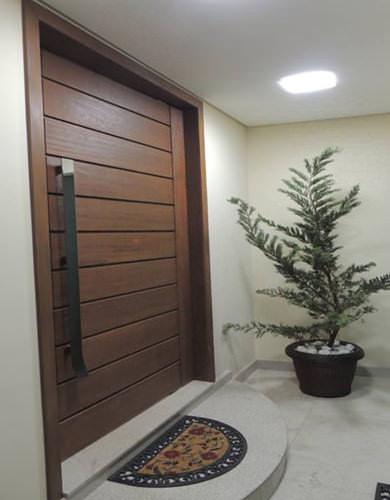 Porta pivotante de madeira com verniz escuro